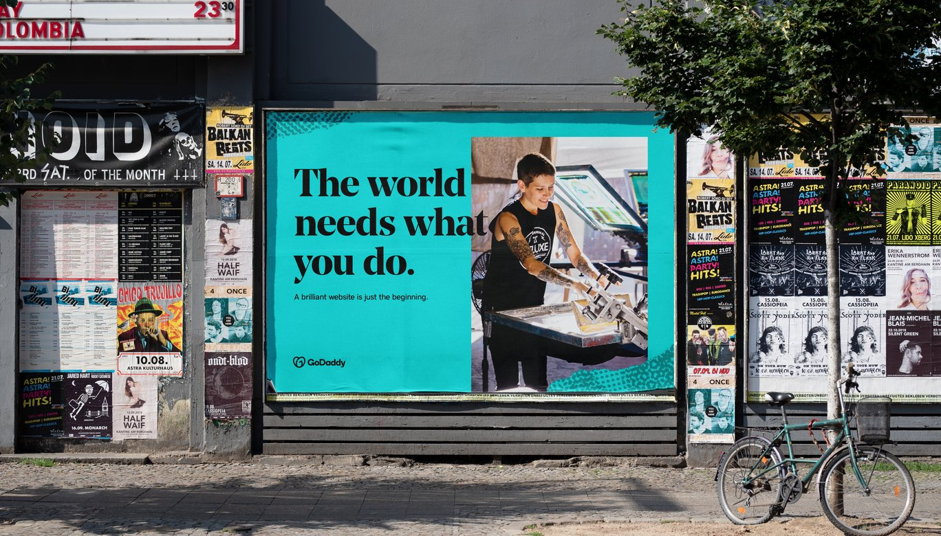 Blue colored billboard of GoDaddy Design showing a small scale entrepreneur working