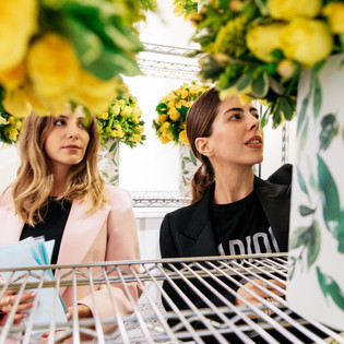 GoDaddy Story of Go - two women standing against out of focus flowers - depth of field image